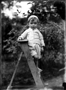 Portrait of small barefoot boy on a wooden ladder